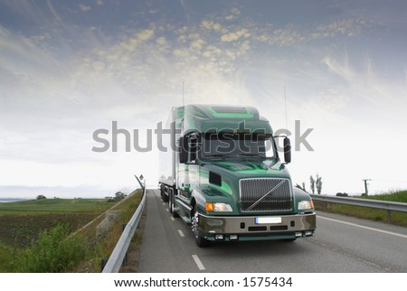 giant lorry, truck on bridge-road under dramatic weather - stock photo