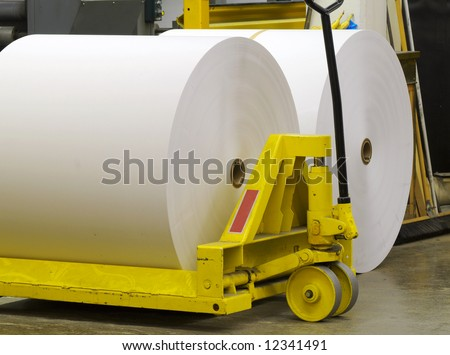 Giant paper rolls waiting to be put on a printing press - stock photo