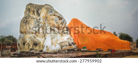Giant Reclining Buddha in Wat Lokayasutharam. Ayutthaya historical park. Panorama - stock photo
