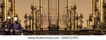 giant refinery with two oil and gas workers at sunset , panoramic view - stock photo
