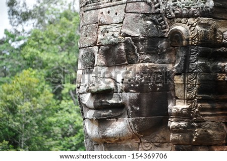 Giant Stone Face at Bayon Temple in the Angkor Thom Temple Complex in Cambodia - stock photo
