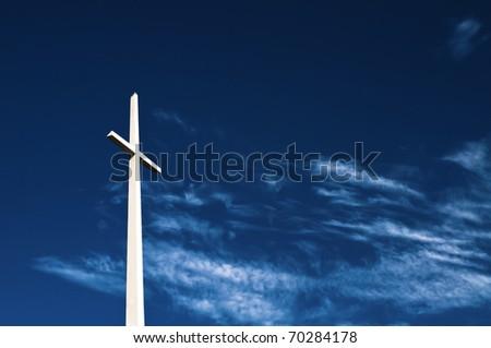 Giant white cross on deep blue sky - stock photo