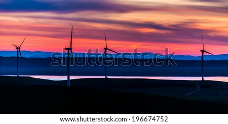Giant wind turbines standing up the hills near the waterside of Lake George, NSW, Australia - stock photo