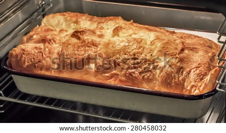 Gibanica cheese crumpled pie, made of crumpled Filo pastry layers, filled with mixture of soft and matured cow cheese, eggs, Feta Cheese, sour cream, and often Kaymak (similar to clotted cream). - stock photo