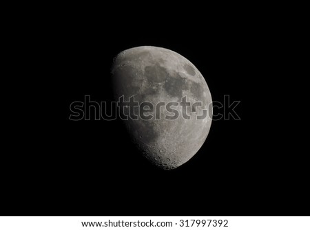 Gibbous moon over dark black sky seen with a telescope from northern emisphere at night - stock photo