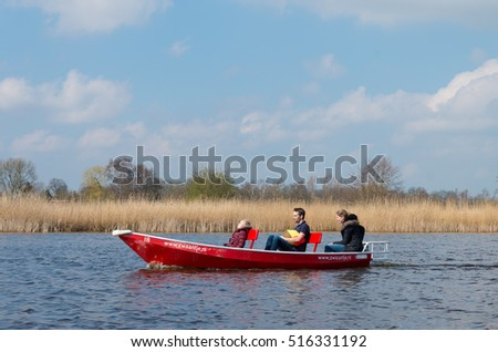 GIETHOORN, NETHERLANDS - APRIL 3, 2016: Unknown family enjoying their boating trip around Giethoorn, also called the Venice of the netherlands