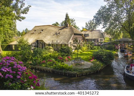 "GIETHOORN, NETHERLANDS - AUGUST 05 2013: Unknown visitors in the sightseeing boating trip in a canal in Giethoorn. The beautiful houses and gardening city is know as ""Venice of the North"". - stock photo"