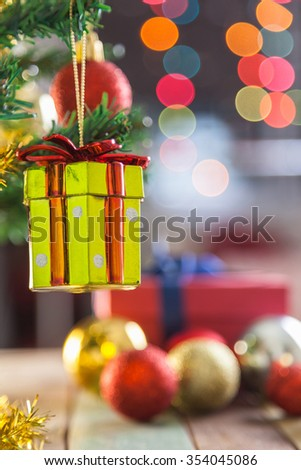 Gift box agains christmas decoration and bokeh background - stock photo