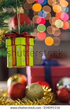 Gift box agains christmas decoration background - stock photo