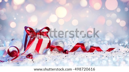 Gift Box And Baubles On Snow With Shiny Background