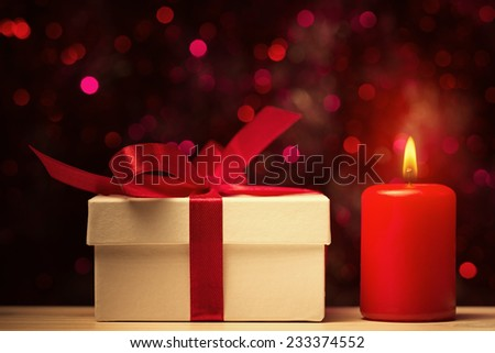 Gift box and candle against defocused lights - stock photo