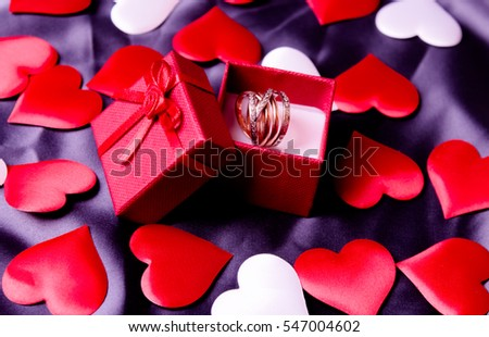 Gift box and decorative hearts on black background