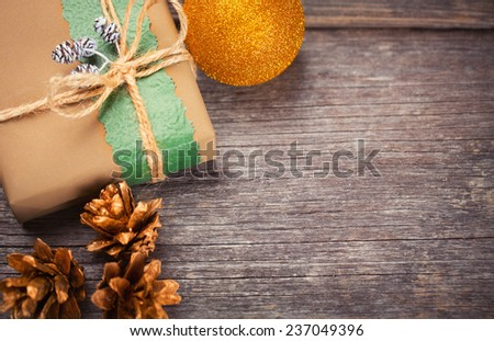 Gift box and pine cones on wooden table