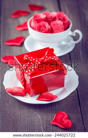 Gift box and pink roses in a cup and red beads on wooden background. Vintage color toning.