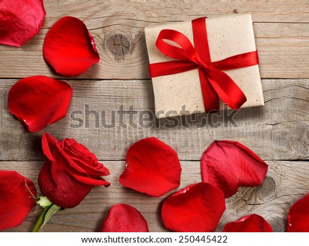 Gift box and red rose on wooden background - stock photo