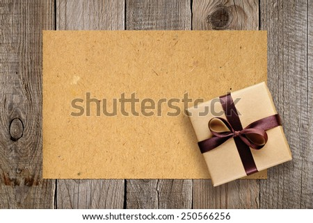Gift box and vintage paper on old wooden background - stock photo