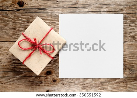 Gift box and white blank paper on wooden background - stock photo