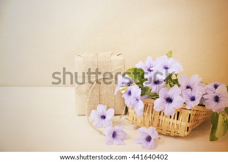 Gift box beautiful bouquet of bright purple flowers in basket on wooden table,vintage tone.
