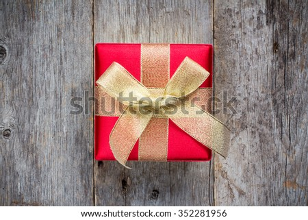 Gift box golden red bow on wood   background, top view