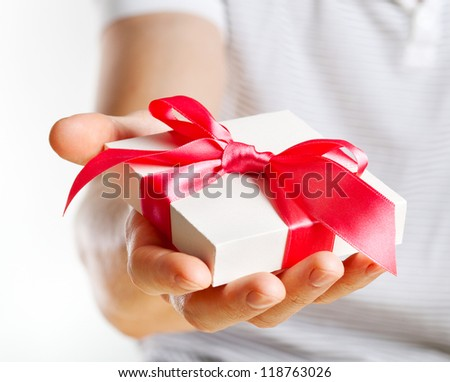 Gift box in man's hand with red ribbon - stock photo