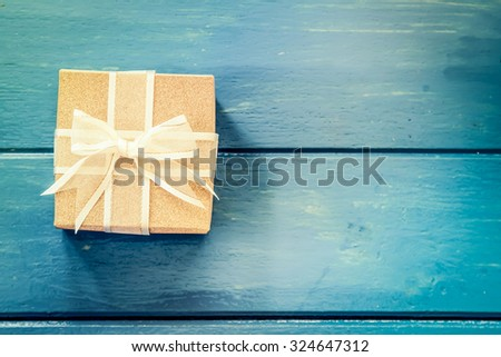 Gift box on blue wooden table,vintage filter - stock photo