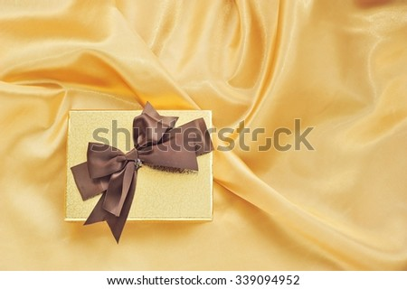 Gift box on gold fabric background.