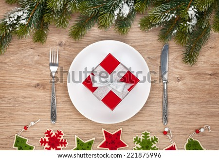Gift box on plate, fir tree and christmas decor over wooden table background - stock photo