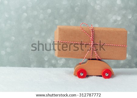 Gift box on toy car. Christmas holiday celebration concept - stock photo
