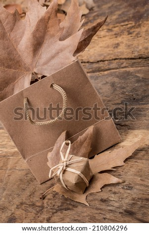 gift box, shopping bag and dried leafs on wooden surface