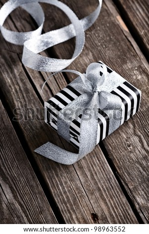 Gift box tied big silver bow with curved silver ribbon on old wooden background. - stock photo
