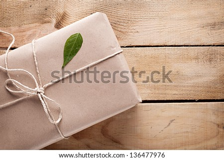 gift box with a green leaf on it on wooden background - stock photo
