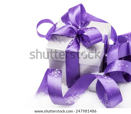 Gift box with a lilac bow on snow isolated on the white - stock photo