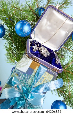 Gift box with a necklace on a New Year tree - stock photo