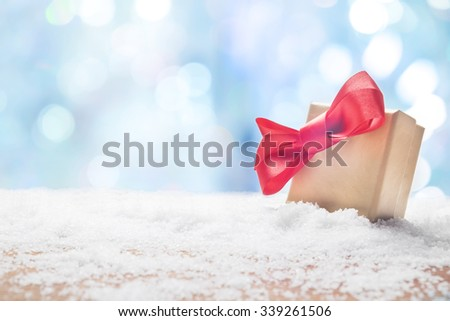 Gift box with a red bow standing in fresh snow against a background bokeh of twinkling party lights.