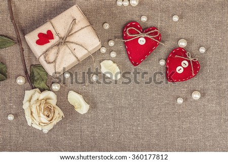 gift box with a white dry rose and two red hearts on sacking, copy space, Valentines Day background