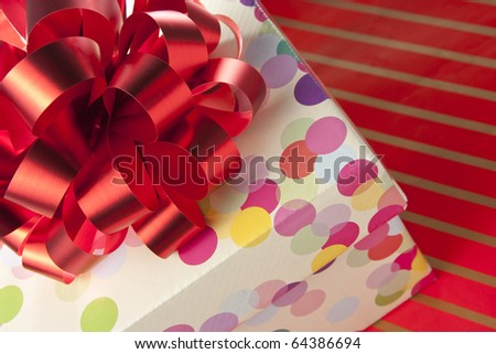 Gift box with big red bow on red striped paper - stock photo