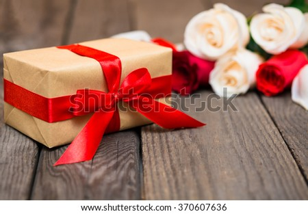 Gift box with blured red and white roses on a dark wooden background. Women' s day, Valentines Day, Mothers day. Copy space, selective focus. Natural optical blur  - stock photo