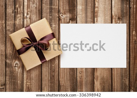 Gift box with bow and greeting card on wooden background top view - stock photo