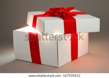 Gift box with bright light on it on grey background