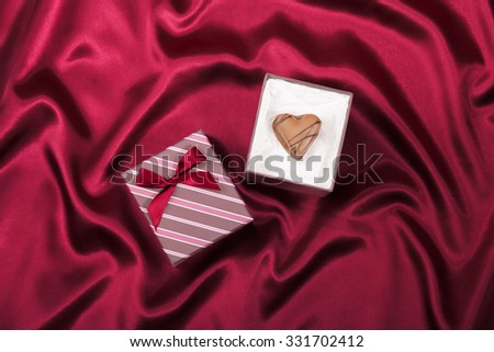 Gift box with chocolate candy heart on red satin background - stock photo