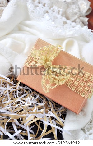 Gift box with golden ribbon on white scarf background
