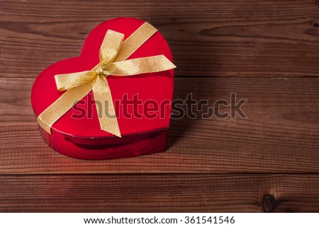 gift box with heart shape on wood - stock photo