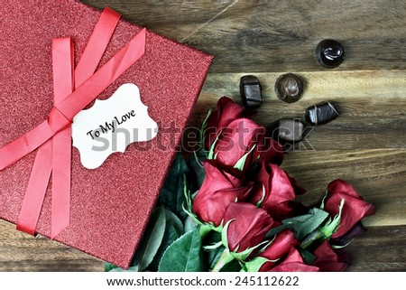 Gift box with long stem red roses and chocolates over an old wooden background with room for copy space. - stock photo