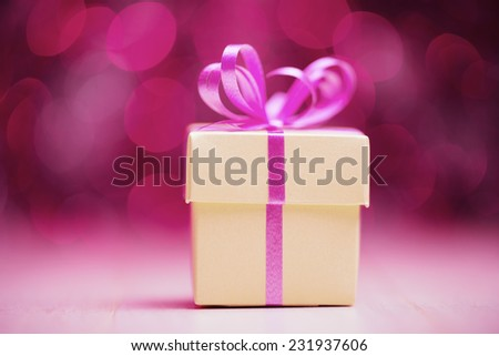 Gift box with pink bow against defocused lights - stock photo
