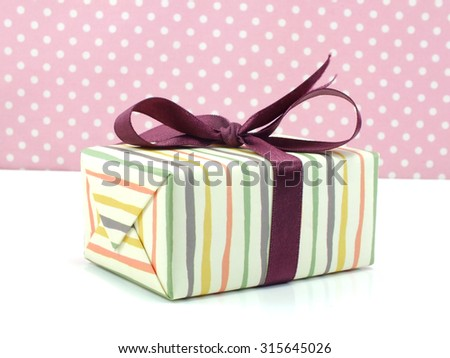 gift box with purple bow on white and sweet polka dot background - stock photo