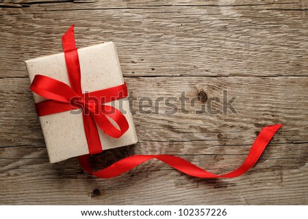 Gift box with red bow on wood background - stock photo