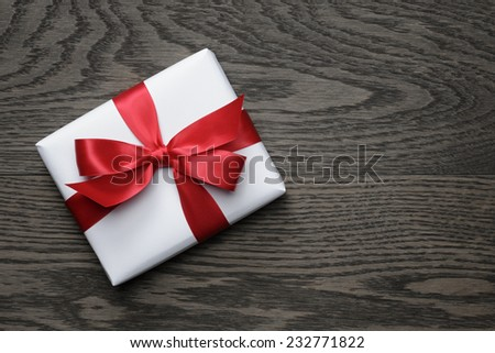 gift box with red bow on wood table, top view - stock photo