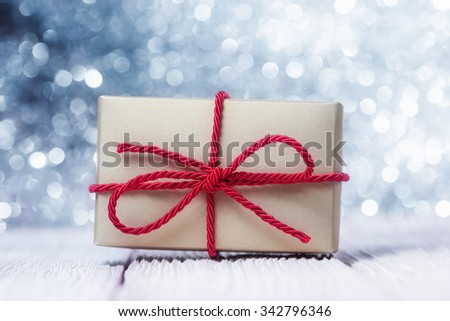 Gift box with red cord over abstract defocused lights - stock photo