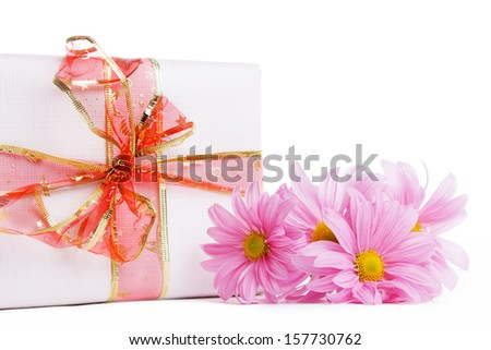 Gift box with red ribbon and pink daisies isolated on white - stock photo