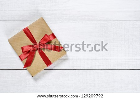 Gift box with red ribbon over white wooden background - stock photo